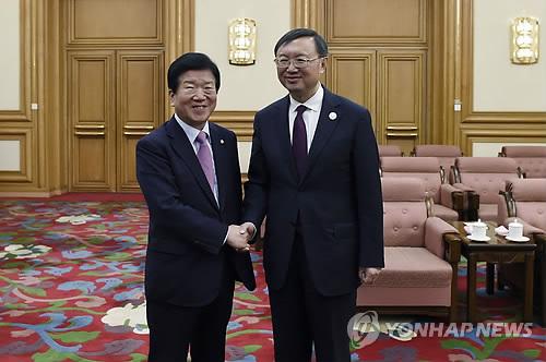 5月15日,在北京中南海,朴炳锡(左)与杨洁篪亲切握手。(韩联社/法新社)