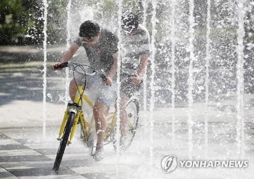 분수 사이로 자전거를 타는 모습