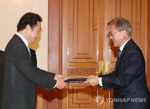 李首相に任命状を授与する文大統領=31日、ソウル(聯合ニュース)