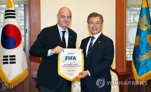 6月12日下午,在青瓦台,韩国总统文在寅与国际足联主席因凡蒂诺(左)合影。(韩联社)
