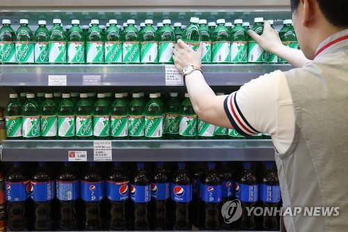 마트 매장에서 직원이 탄산음료 판매대를 정리하는 모습
