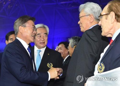 Le président Moon Jae-in échange une poignée de main avec le membre nord-coréen du Comité international olympique (CIO) Chang Ung le samedi 24 juin 2017 lors de la cérémonie d'ouverture des Championnats du monde de taekwondo 2017.