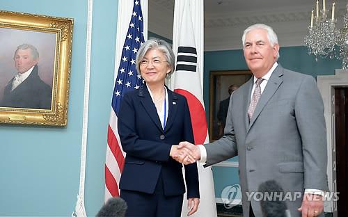 资料图片:6月28日(当地时间),在华盛顿,韩国外交部长官康京和(左)和美国国务卿蒂勒森亲切握手合影。(韩联社/韩国外交部提供)