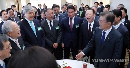 6月28日,韩国总统文在寅(右)在美国华盛顿亚当斯甘草酒店与随行企业家们交谈。(韩联社)