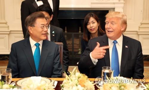 当地时间6月29日,在美国白宫,文在寅(左)和特朗普在晚宴上亲切对话。(韩联社)