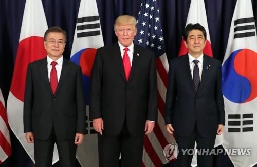 韓米日の首脳は7月上旬にドイツ・ハンブルクで夕食会を兼ねた会談を行った。左から文大統領、トランプ大統領、安倍首相=(聯合ニュース)