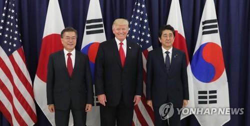 Le président Moon Jae-in, le président américain Donald Trump et le Premier ministre japonais Shinzo Abe posent pour une séance photos au consulat général des Etats-Unis à Hambourg, en Allemagne, le jeudi 6 juillet 2017, avant un dîner officiel.