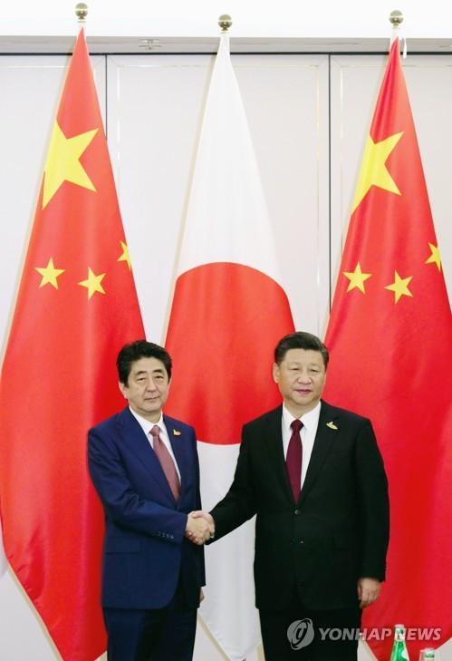 악수하는 시진핑(오른쪽)과 아베