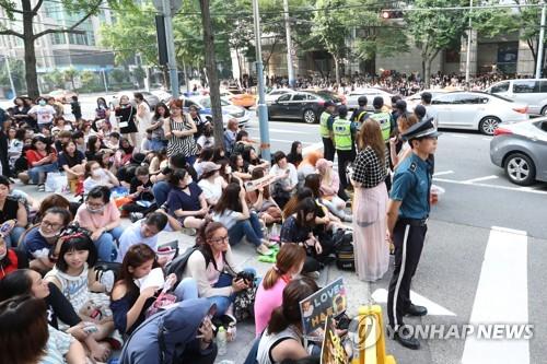 14日上午,在首尔地方警察厅门口,大批歌迷一早开始等待东海退伍。(韩联社)