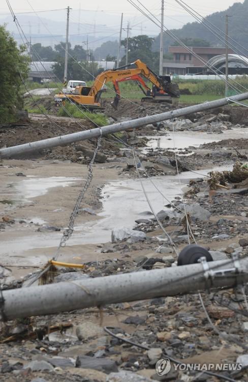 Downpour knocks down utility poles