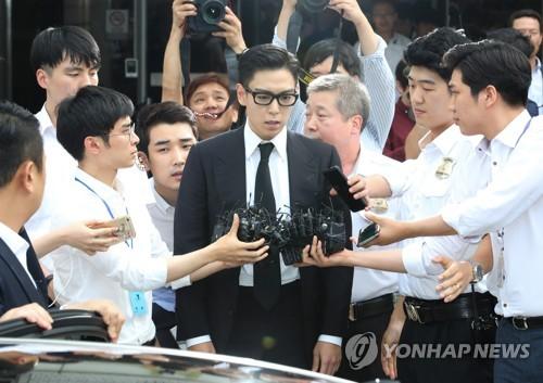 昨年7月、判決公判が開かれたソウル中央地裁で報道陣に囲まれるT.O.P=(聯合ニュース)
