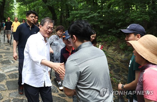 最初の夏の休暇には江原道・平昌の山を訪れた。登山客とあいさつを交わす文大統領(資料写真、青瓦台提供)=(聯合ニュース)