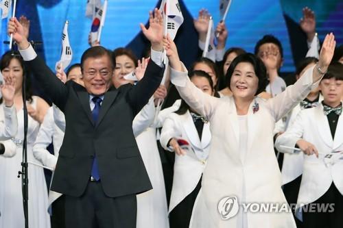 光復節の記念式典で万歳三唱する文大統領(左)と夫人=15日、ソウル(聯合ニュース)