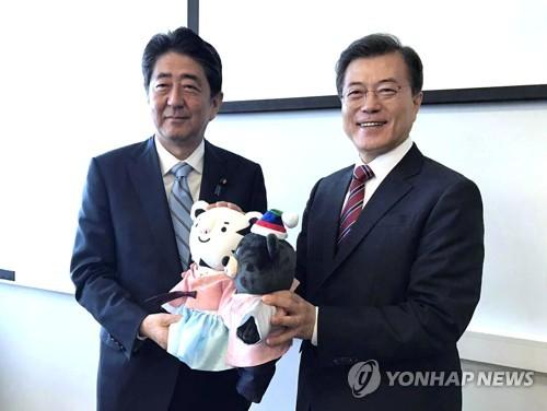 Le président Moon Jae-in pose pour une séance photos avec le Premier ministre japonais Shinzo Abe le jeudi 7 septembre 2017 à l'université fédérale d'Extrême-Orient à Vladivostok en Russie, après avoir offert à ce dernier les mascottes des Jeux olympiques d'hiver de PyeongChang, Soohorang (tigre blanc) et Bandabi (ours noir).