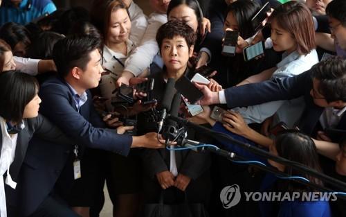 ソウル中央地検前で報道陣に囲まれるキム・ミファさん=19日、ソウル(聯合ニュース)