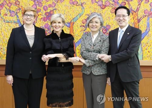 手を取り合う、(右から)韓国の宋永武国防部長官と康京和外交部長官、オーストラリアのビショップ外相とペイン国防相=13日、ソウル(聯合ニュース)
