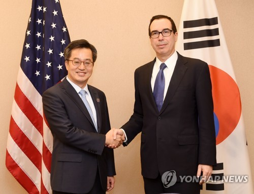 握手を交わす金副首相とムニューシン長官(企画財政部提供)=(聯合ニュース)