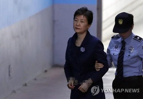 资料图片:10月16日上午,在首尔中央地方法院,韩国前总统朴槿惠(左)被押往法庭。(韩联社)