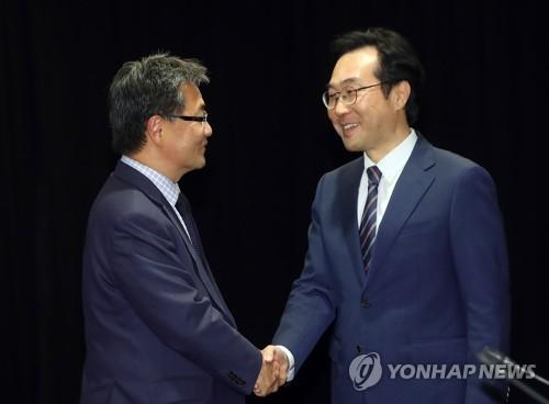 Le représentant sud-coréen aux pourparlers à six sur le dossier nucléaire nord-coréen, Lee Do-hoon (à droite), échange une poignée de main avec son homologue américain, Joseph Yun, le mercredi 18 octobre 2017 à l'hôtel Lotte dans le centre de Séoul, lors de la réunion tripartite Corée du Sud-Etats-Unis-Japon.