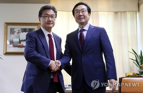10月20日にソウルで会合し、握手を交わす李度勲氏(右)とジョセフ・ユン氏=(聯合ニュース)