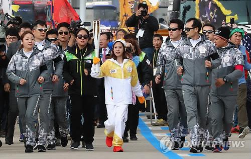 La patineuse artistique You Young, premier relayeur de la flamme des Jeux olympiques d'hiver de PyeongChang 2018, court sur le pont d'Incheon le mercredi 1er novembre 2017.