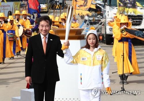 Le premier relayeur de la flamme olympique, «l'espoir du patinage artistique» You Yong (à gauche), et le Premier ministre Lee Nak-yon posent pour une séance photos après la passation de la flamme le 1er novembre 2017, à 100 jours du début des Jeux olympiques d'hiver de PyeongChang 2018.