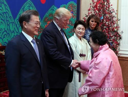 夕食会でトランプ大統領と握手する慰安婦被害者の李容洙(イ・ヨンス)さん=(聯合ニュース)