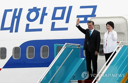 ベトナム中部のダナン国際空港に到着後、手を振る文大統領夫妻=10日、ダナン(聯合ニュース)