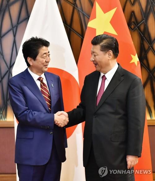손잡은 시진핑(오른쪽)과 아베