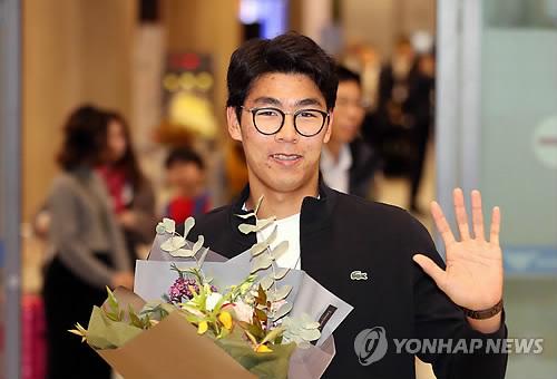 仁川国際空港に到着後、笑顔で手を振る鄭現=13日、仁川(聯合ニュース)