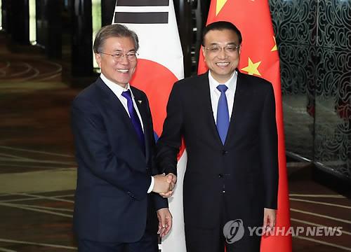 笑顔で握手を交わす文大統領と李首相=13日、マニラ(聯合ニュース)