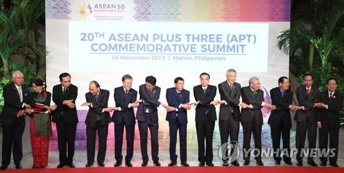 ASEANプラス3首脳会議で記念撮影する各国首脳ら。左から5人目が文在寅大統領=14日、マニラ(聯合ニュース)