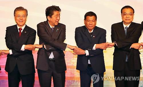 기념촬영 손잡는 문 대통령과 아베 총리