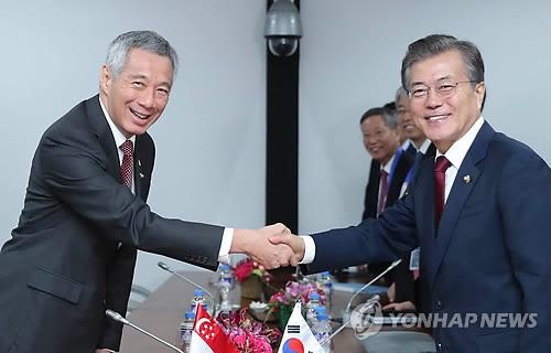 Le président Moon Jae-in et le Premier ministre singapourien Lee Hsien Loong échangent une poignée de main au Philippine International Convention Center (PICC) à Manille, lors de leur sommet bilatéral.