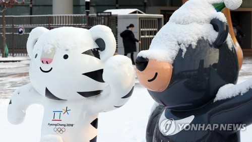 Les mascottes des Jeux olympiques et paralympiques d'hiver de PyeongChang 2018, Soohorang (tigre blanc) et Bandabi (ours noir), installées devant le complexe gouvernemental à Sejong, portent un chapeau de neige le mercredi 6 décembre 2017, alors que la neige est tombée pendant la nuit.