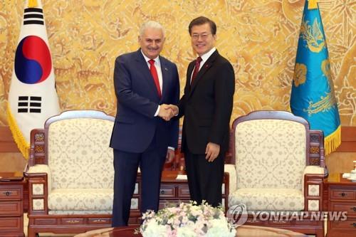 ユルドゥルム首相と握手を交わす文大統領(右)=6日、ソウル(聯合ニュース)