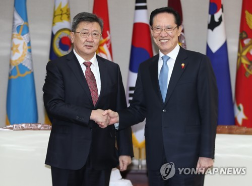 握手を交わす宋長官(右)とエンフボルド国防相=7日、ソウル(聯合ニュース)