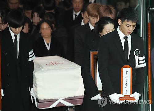 12月21日上午,在首尔峨山医院,SHINee成员珉豪(右)手捧钟铉的牌位。(韩联社)