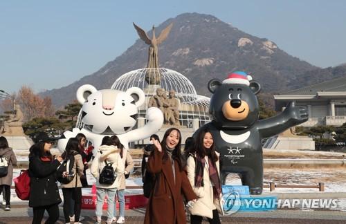 Des citoyens prennent des photos devant les mascottes des Jeux olympiques de PyeongChang 2018, Soohorang (tigre blanc) et Bandabi (ours noir), installés devant le palais présidentiel Cheong Wa Dae le jeudi 21 décembre 2017.