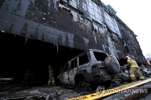 現場で消防隊員が捜索作業を行っている=22日、堤川(聯合ニュース)