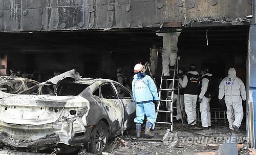 火災が起きたビルの駐車場で鑑識を行う関係者=22日、堤川(聯合ニュース)