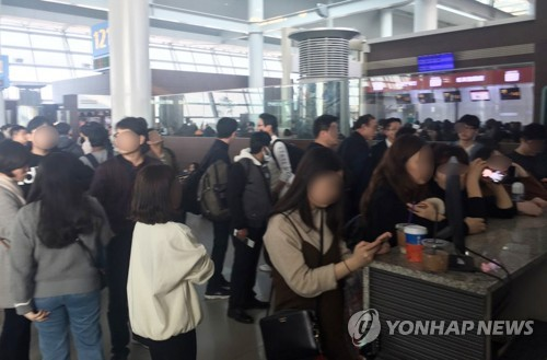 12月23日,在韩国仁川国际机场,浓雾导致航班延误,大量乘客在登机口处等待航空公司通知。(韩联社/读者提供)