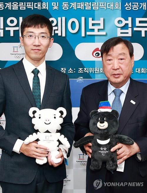 1月9日,李熙范(右)与张�辞┦鹦�议后合影留念。(韩联社/平昌冬奥组委会提供)