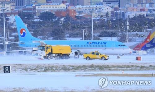 済州空港滑走路の除雪作業の様子=11日、済州(聯合ニュース)
