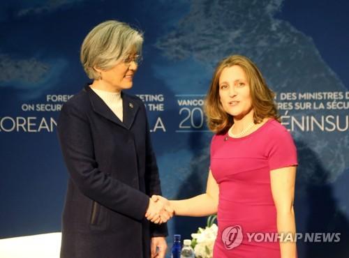 カナダのフリーランド外相(右)と握手を交わす康京和長官=15日、バンクーバー(聯合ニュース)