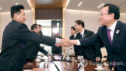 実務会談で握手を交わす韓国(右)と北朝鮮の出席者(統一部提供)=17日、ソウル(聯合ニュース)