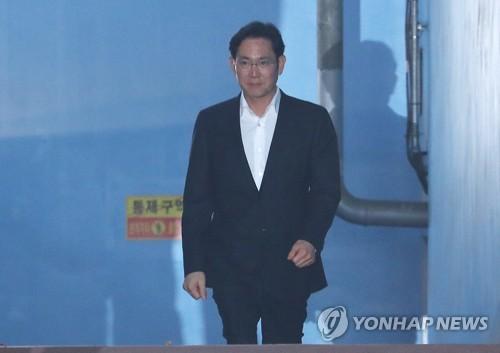 2月5日,在首尔高等法院,李在�F获释后走出法院。(韩联社)