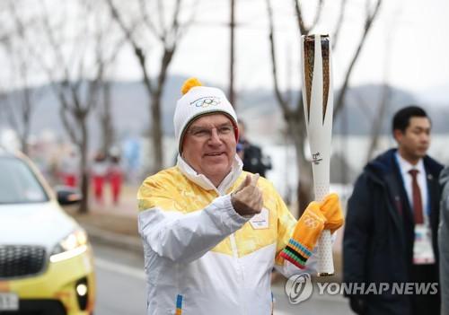 トーチを掲げるバッハ会長=9日、平昌(聯合ニュース)