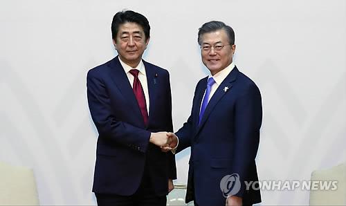 文在寅大統領(右)は今月9日に安倍晋三首相と会談した=(聯合ニュース)