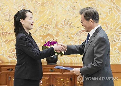 2月10日上午,在韩国青瓦台,朝鲜最高领导人金正恩的胞妹、劳动党中央委员会第一副部长金与正(左)向韩国总统文在寅转交金正恩的亲笔信。(韩联社)